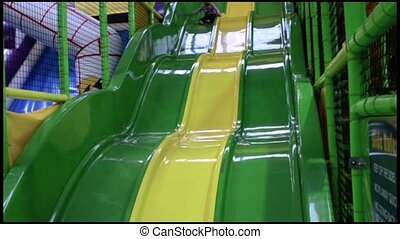 Little girl slid on a giant slid in indoor playground