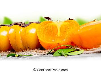 Kaki fruit - Photo of kaki fruit with leaves on burlap with...