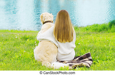 Silhouette of owner and Golden Retriever dog sitting together on the grass near river in sunny summer day