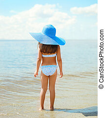 Back view of beautiful little girl child in swimsuit and straw hat on the beach near sea