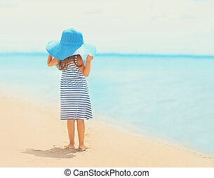 Pretty little girl in dress and straw hat enjoying on the beach near sea in sunny summer day