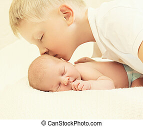 Eldest brother kissing youngest baby, two children lying together on the bed at home