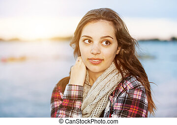 Young brunette woman at sunset