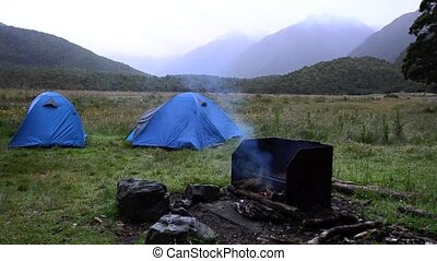 Outdoor campfire near a tent - An outdoor campfire near a...