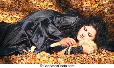 Woman In Black Cuddling A Furtail Lying In Autumn Forest -...