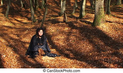 Woman In Black Playing With Leaves In Autumn Forest