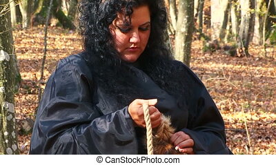 Woman In Black Tying Rope To A Fur Tail In Autumn Forest