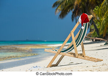 Sun lounger with Santa hat at beautiful tropical beach with...