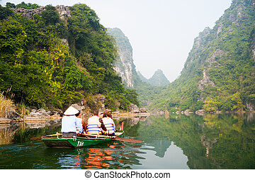 Trang An Grottoes - A touristic boat moves through a river...