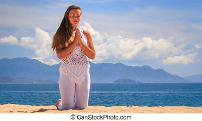 blonde girl in lace demonstrates yoga asana stands on knees
