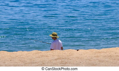 fisherman in hat fishes with rod on sand beach against azure...