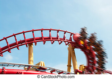 Roller coaster ride under blue sky with motion effect applied
