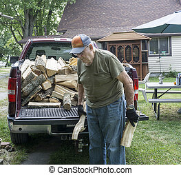 Elderly Man Helping Stack Firewood - Elderly man helping...
