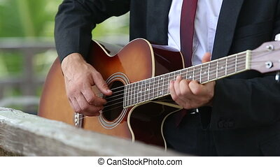 acoustic guitar which man in suit and tie plays - acoustic...