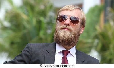blonde bearded man in black suit and glasses plays guitar...