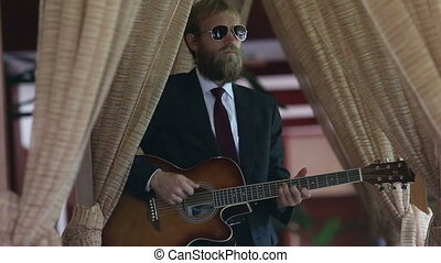 bearded man in black suit plays guitar among curtains -...