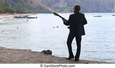 guitarist plays against beach with longtail boats and...