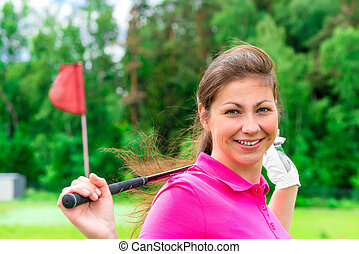 Female golfer with with a golf club smiling