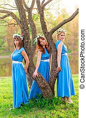 Girls around a tree near the lake on a summer evening