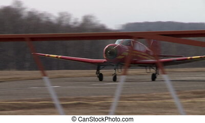 View of red single-engine plane takes off from runway