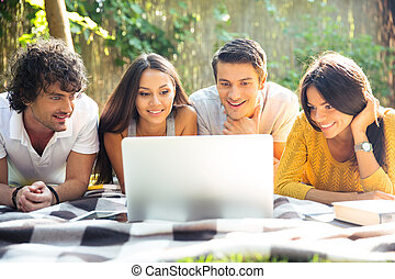 Friends using laptop outdoors - Smiling friends using laptop...