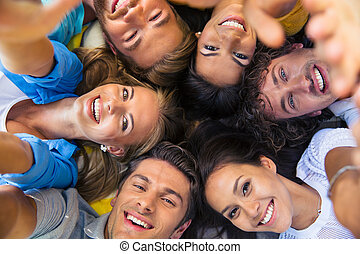 Friends lying together in a circle - Group of happy friends...