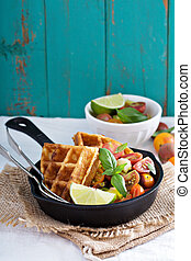 Savory waffles with cheese and cornmeal served with tomato...