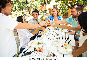 Friends making toast around table - Group of a young friends...