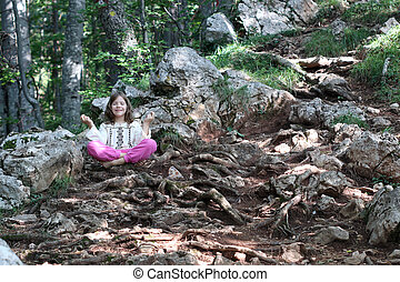 little girl meditating in the forest