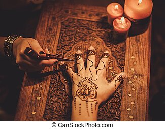 Drawing process of henna menhdi ornament on womans hand