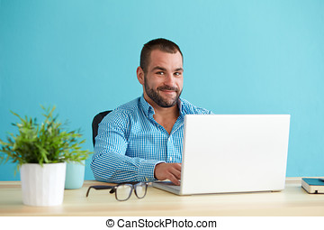 Young businessman working in modern office on computer