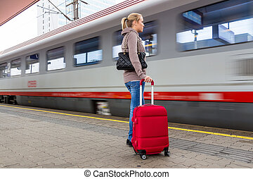 woman waiting for train on railway station - a young woman...