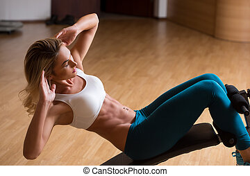 Beautiful young woman in sports clothing training her abs