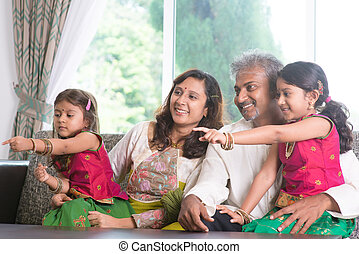 Family pointing away - Happy Indian family at home. Asian...