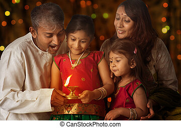 Celebrating Diwali - Indian family in traditional sari...