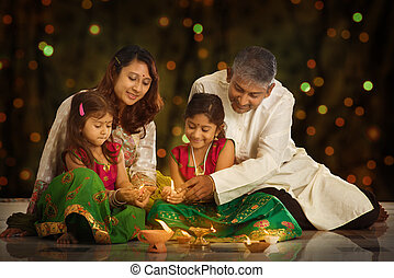 Indian family celebrating Diwali, fesitval of lights -...