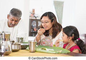 Indian family eating banana leaf rice - Indian family dining...