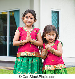 Cute Indian girls in sari greeting - Cute Indian girls...
