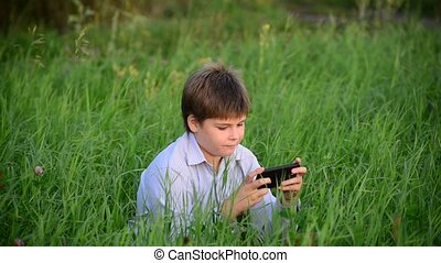 Teen boy with surprise looks at smartphone