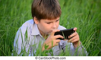 Teenage boy uses a smartphone in meadow in the countryside -...