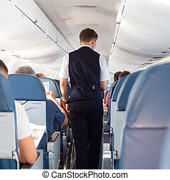 Steward on the airplane - Interior of airplane with...