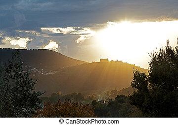Sun rays on a small town - Sun rays through the clouds light...