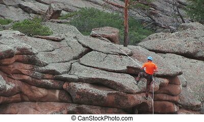 Climber On The Cliff - Man Descends From The Top Of The...