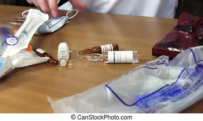 Preparing an Injection - Doctor chooses vial for injection