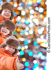 happy winter kids against colorful lights - The collage is...