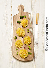 duchess potato on a wooden board - home made duchess potato...