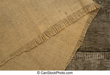 Burlap on rustic wooden background Top view