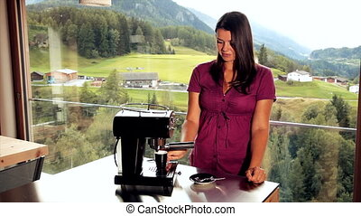 Woman taking coffee from expresso machine at home in the...