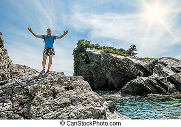 man arms outstretched standing on a rock by the sea