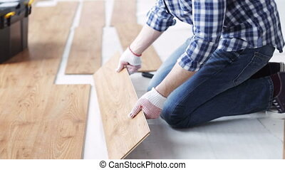 close up of man installing wood flooring